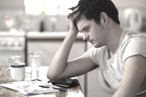 Young man at kitchen table with head on his hand fretting over student loan and other bills laying in front of him