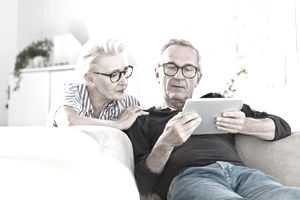 Senior couple watching digital tablet together at home