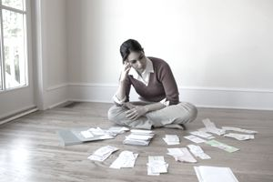 Woman looking at bills and financial statements spread out around her on the floor.