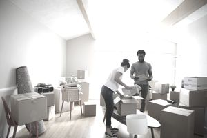 Young couple packing belongings in cardboard boxes