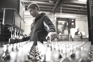 A worker bottles product at a distillery