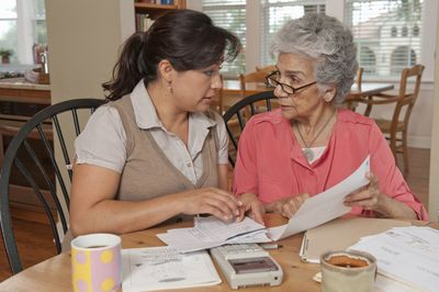 A serious daughter talks to her mother as they sort through financial papers at a table holding a calculator, stacks of papers, and coffee mugs