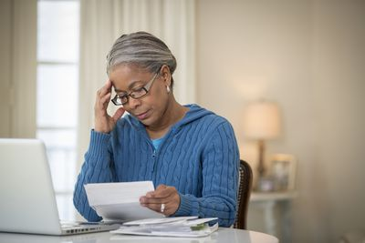 Woman looking overwhelmed while looking at paperwork