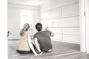 Young couple in new, empty home sitting on floor discussing improvements