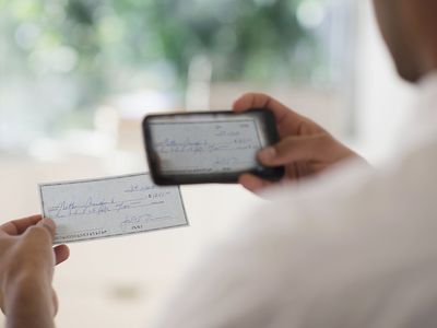 Man taking photo of banking check with cell phone