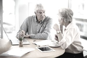 elderly couple talking about financial matters in front of a computer