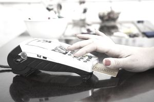 Woman typing in pin number for payment.
