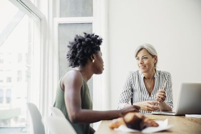 Two friends discuss finances and how to build credit at a table