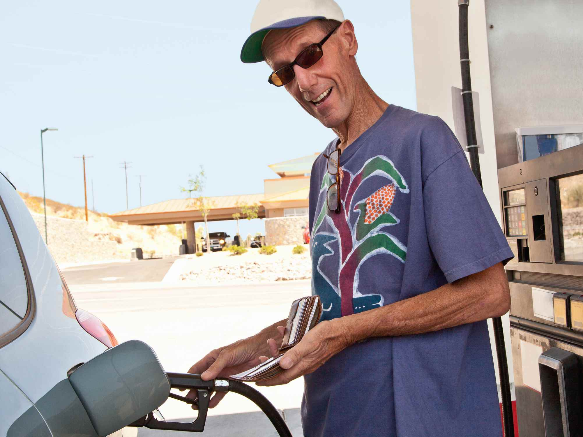 Smiling man pumping gas in the summer during gas price inflation