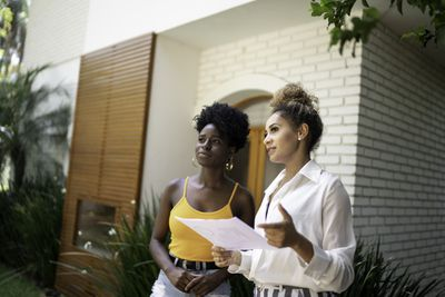 A woman and a real estate agent holding a document have a discussion in front of a home