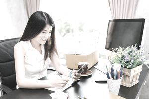 Young cute Asian small business owner work at home office, using mobile phone call, writing confirm purchase order on notebook