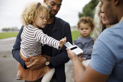 Young family with two children making a purchase using a debit card.