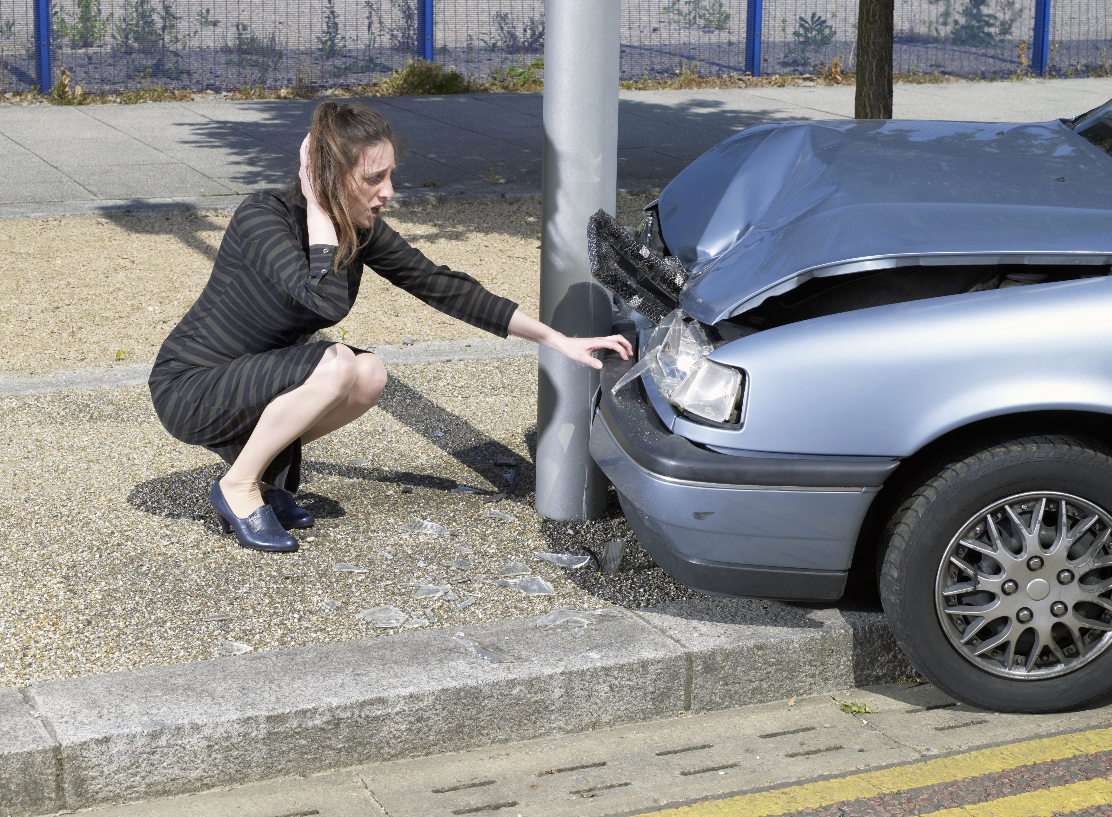 Young woman crouching by car crash by road