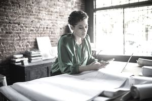Businesswoman looks at her phone in front of architecture blueprints in an office.