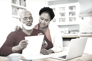 Mature couple managing their retirement paperwork together at home