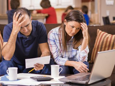 Couple paying monthly bills at home. Frustration.