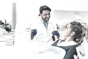 Dentist Preparing to Clean Teeth of a Young Female Patient in Dental Chair