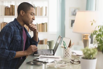 Business owner at home office with laptop