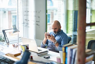 Man looking at cell phone in his office
