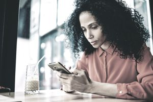 stressed person in red buttoned-up shirt using iPhone at cafe