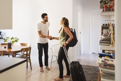 Home owner shakes hands with a visitor at a home-sharing business