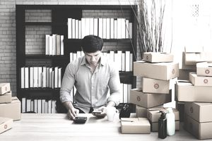 Man working at home preparing merchandise sold online in small business