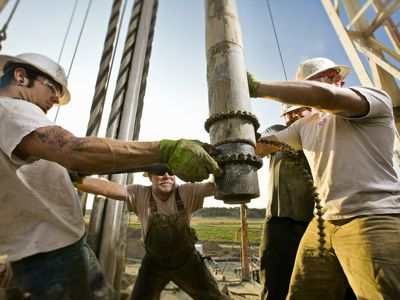 Oil workers use chain to wrangle a petroleum drill into position.