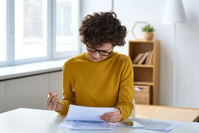 A person with glasses reviews documents in a home office.
