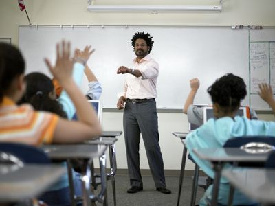Male teacher standing before students (8-10) with hands raised