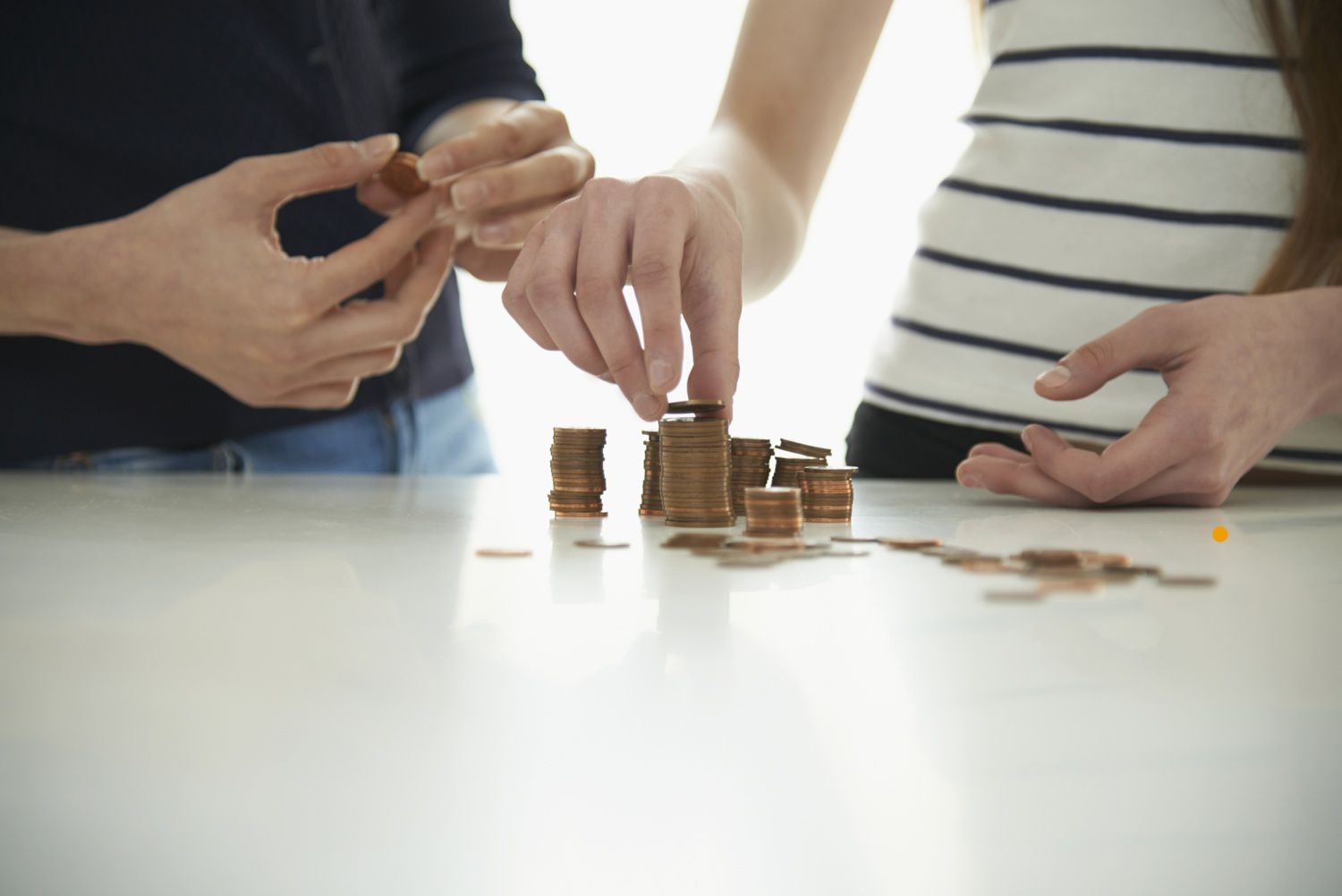 Close-up of the hands of a man and woman stacking coins