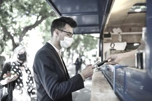 A man in a mask pays for a snack from a food truck using a debit card.