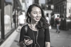 Young woman listening music with cell phone and earphones on a New York street