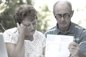 A senior couple reads a bill