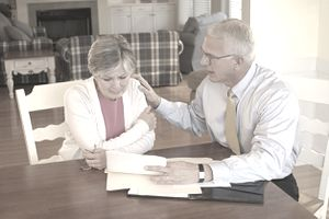 Older couple seated at a kitchen table reviewing papers