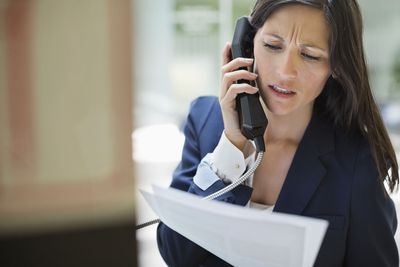 Concerned woman on phone call with debt collector holding papers