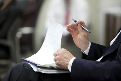 Man's hand holding a pen holding a note pad on his lap