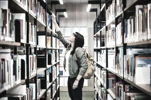 Student Selecting Book From Shelf In Library.