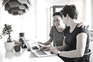 A lesbian couple smile at one another as they sit in their bright kitchen debating how long to keep tax records while looking at a laptop.