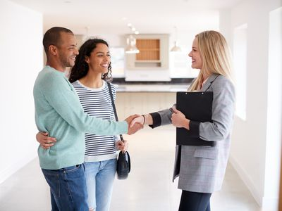 Female Realtor Shaking Hands With Couple Interested In Buying House