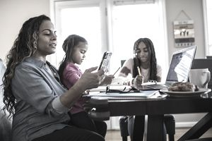Mother working from home while daughters homeschool