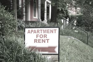 """White and Red """"Apartment for Rent"""" Sign in Front Yard of a House"""