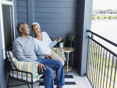 Laughing senior couple on porch overlooking a lake