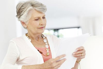 an older woman reading documents pertaining to her deceased spouse's IRA.