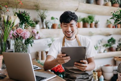 Man in floral shop smiles while reviewing digital tablet