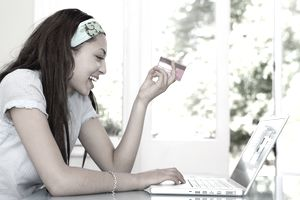 A teenage girl sits in front of a laptop holding a credit card