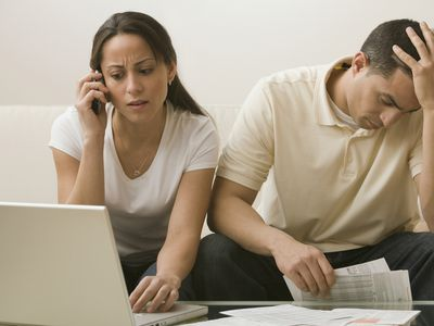 An upset couple sitting on a sofa, frustrated by continued creditor calls after a bankruptcy.