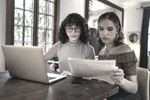 Two people study a document
