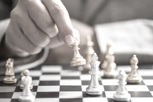 Businessman hand with businessman goal with chess