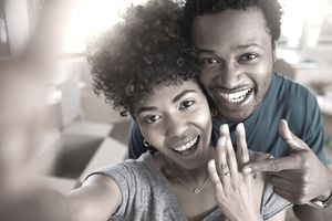 A young couple smiles into the selfie-camera and show off the engagement ring they financed.