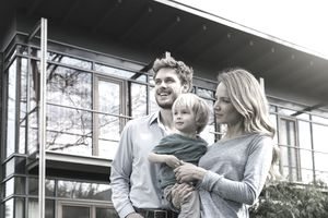 A family stands in front of their new home.